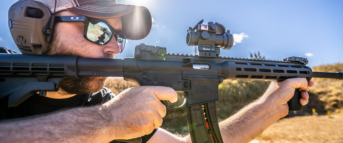 man looking down the scope of an AR