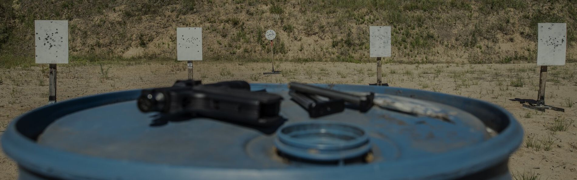 Outdoor Target Range with a Handgun resting on a blue barrel