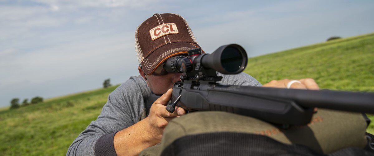 man looking down a rifle scope outside