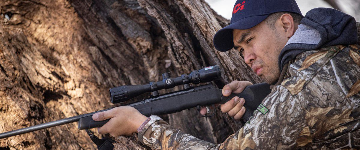 hunt aiming a rifle in the woods