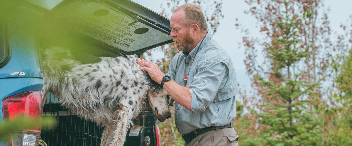 Mike Bartz with a hunting dog in the back of a pick-up