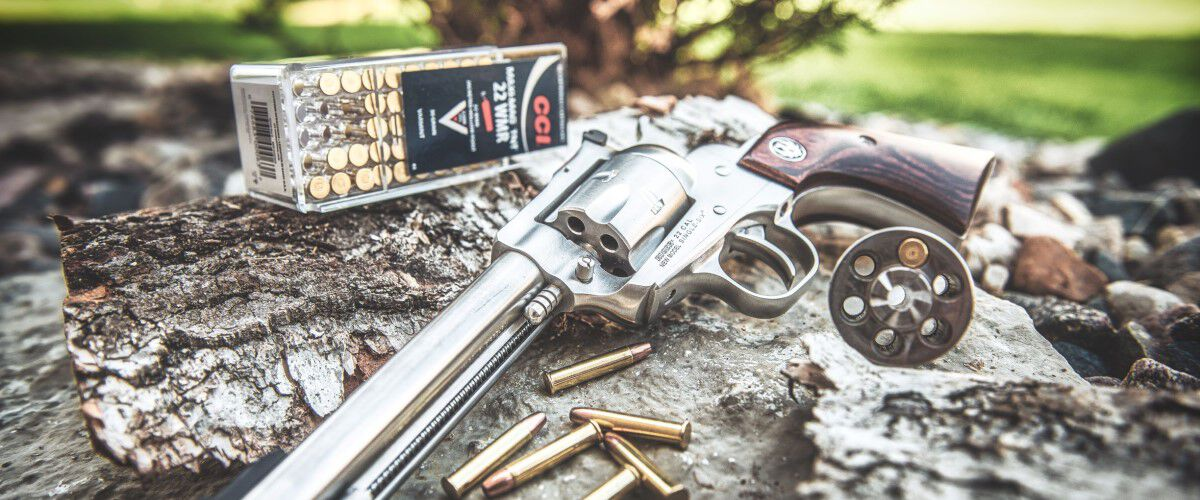 handgun laying on a tree stump with CCI ammo in the background
