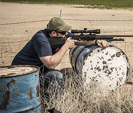 Man pointing rifle while resting in a barrel