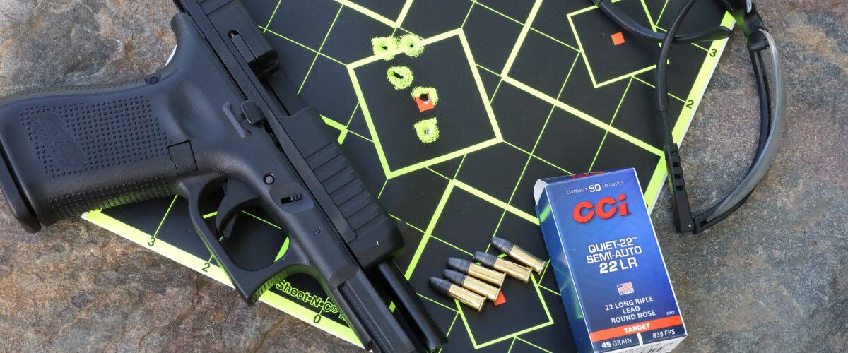 A handgun, glasses and CCI ammo laying on top of a shot target.