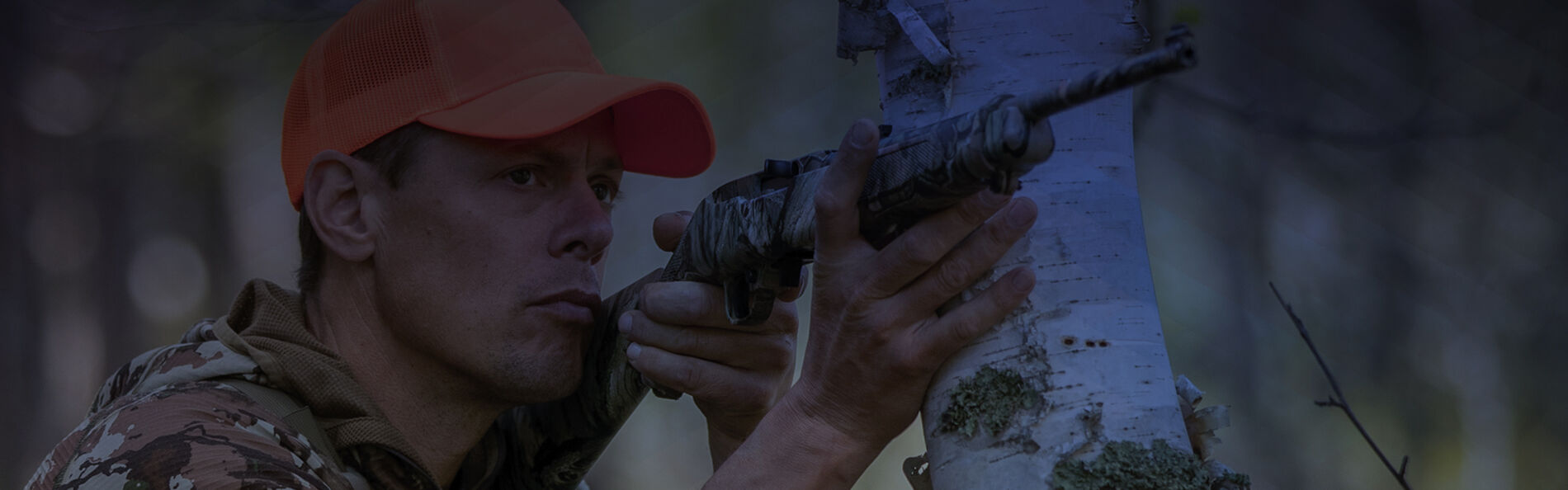 Steven Rinella looking down the iron sights of a rifle with blue overlay