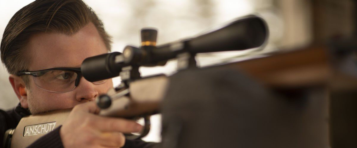 man looking down the scope of a resting rifle