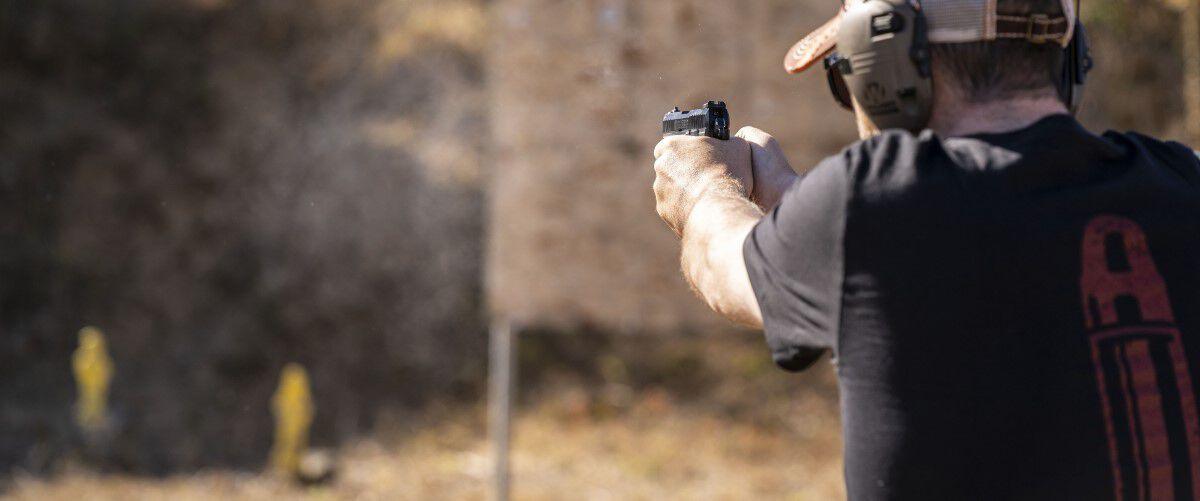 man pointing a handgun at a couple targets at an outdoor range