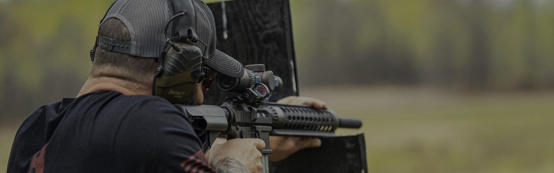 man aiming a rifle that is rested on a wood support