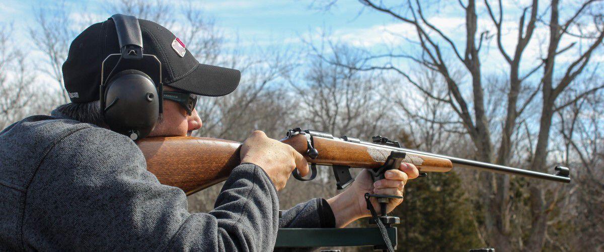 man looking down a rifle iron sights