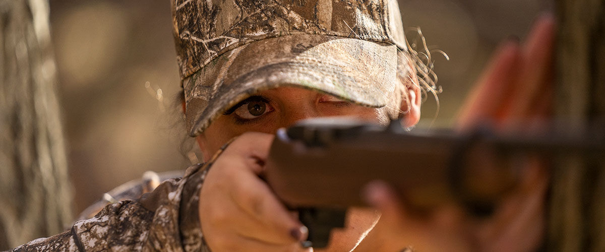 Woman shooting rimfire rifle in the field