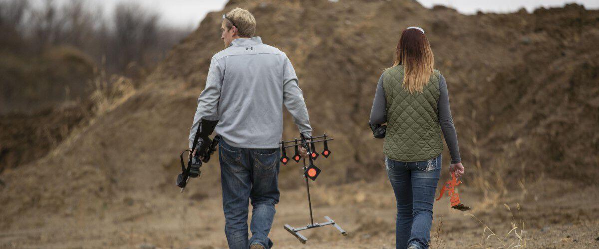 man and women walking outside carrying metal targets