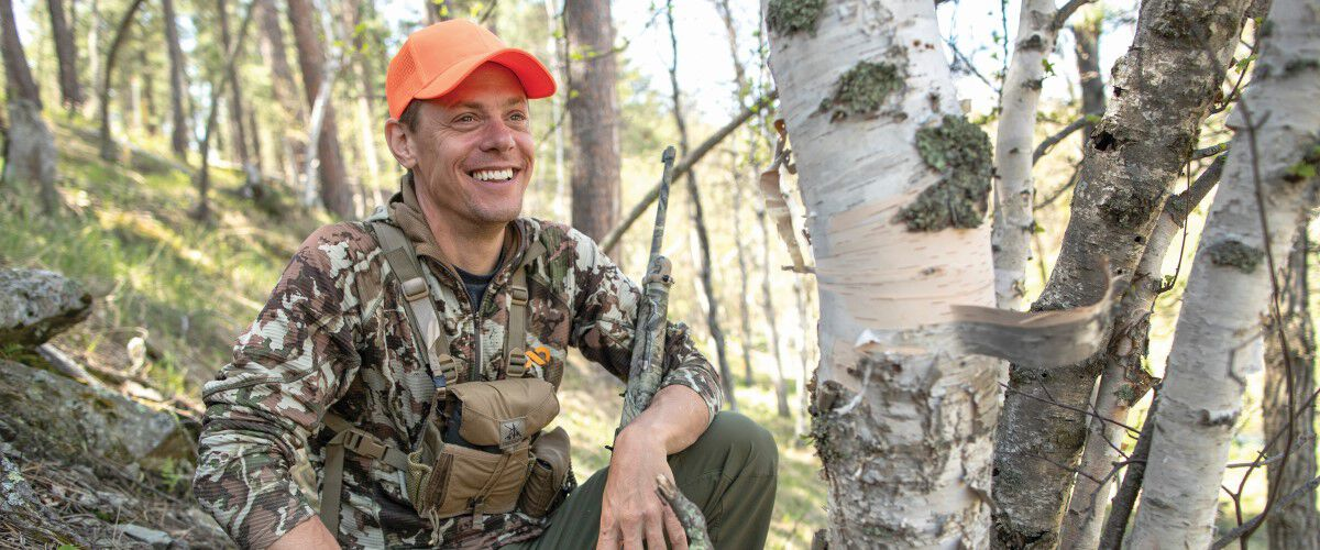 Steven Rinella sitting amoungst trees