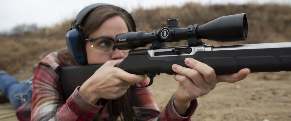 lady in a prone position looking down the scope of a rifle