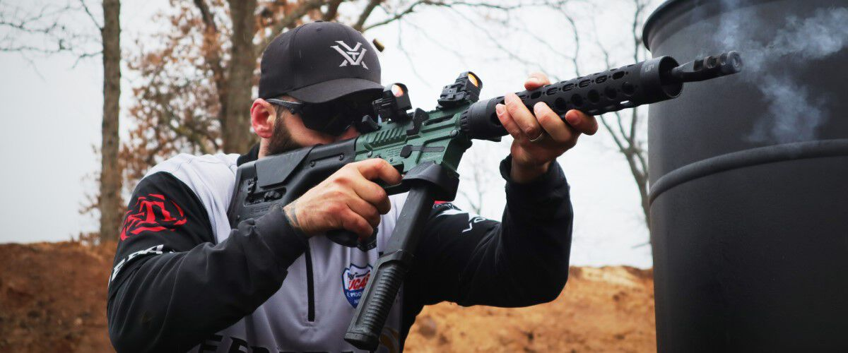 Josh Froelich Shooting A Rifle around a barrel