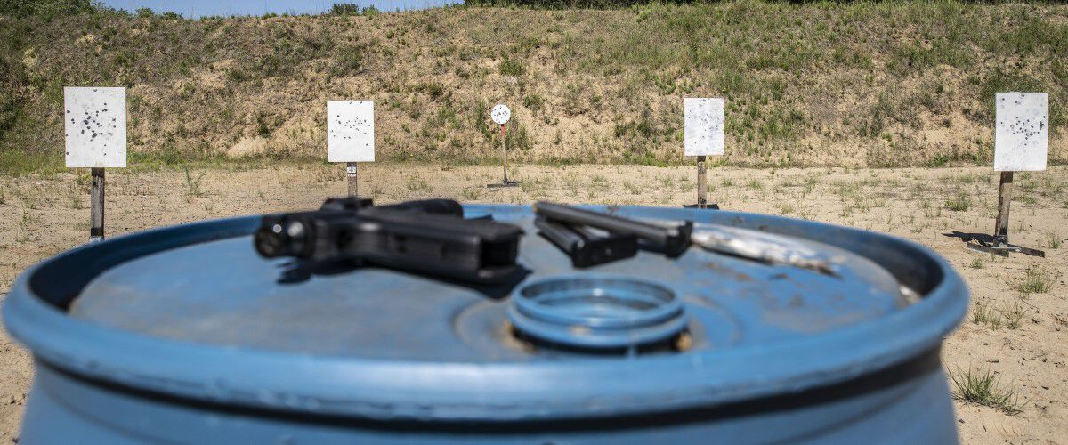 Outdoor Range with handgun resting on a blue barrel