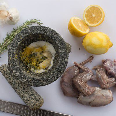 raw squirrel with lemons and other ingrediants in a mortor