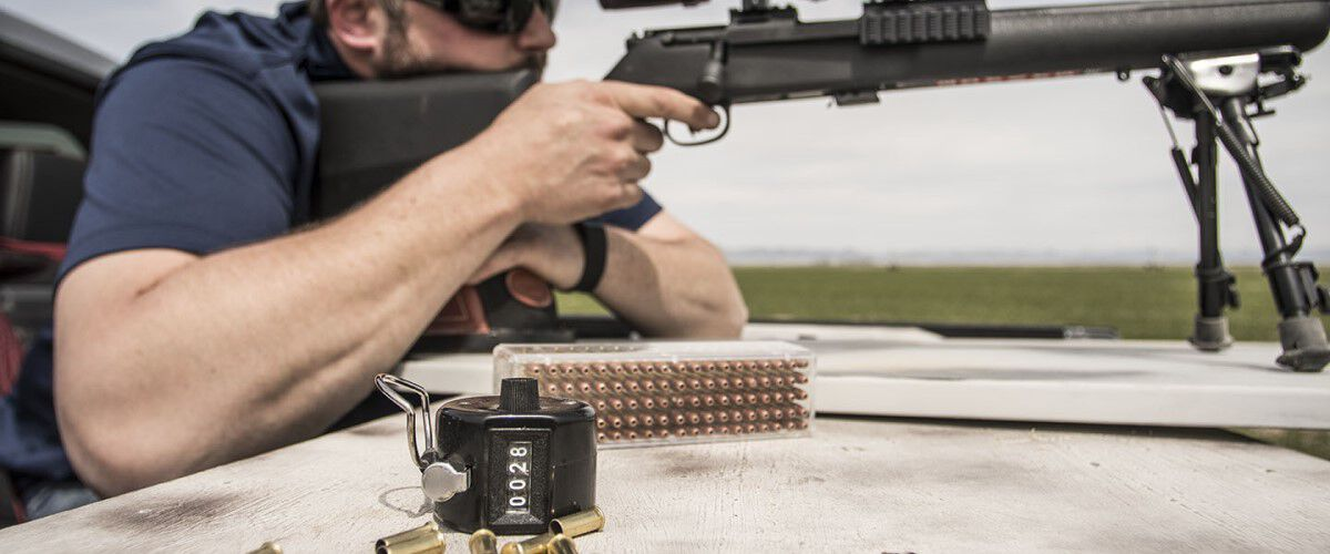 Man looking down a rifle scope with loaded ammo and a counter on the table