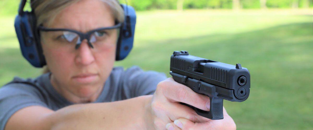 person pointing a handgun